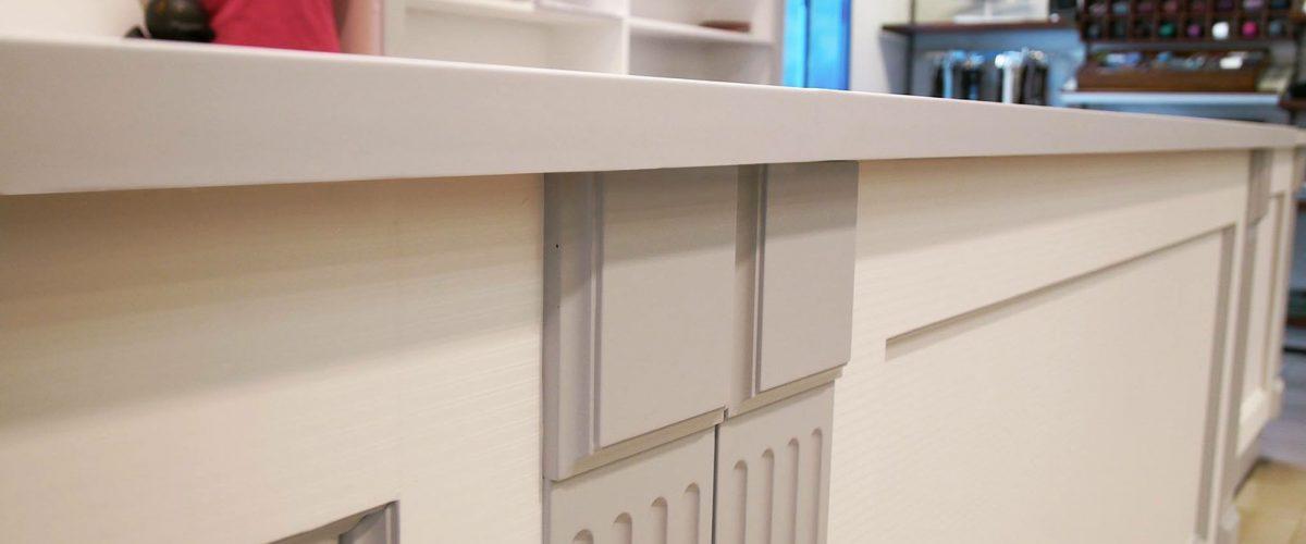 Dettaglio banco cassa bianco e grigio personalizzato