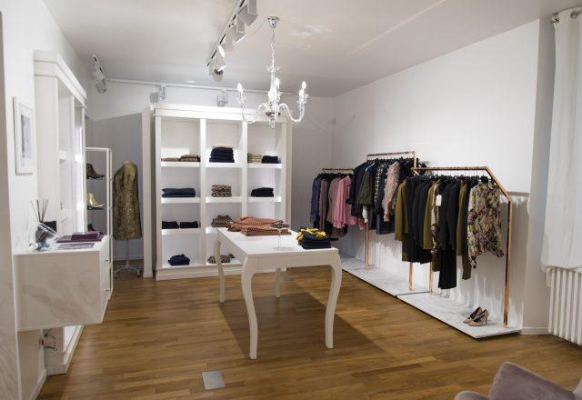 Arredo bianco in stile classico per negozio di abbigliamento da donna